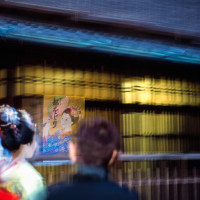 Maiko walking passing by poster Kyoto